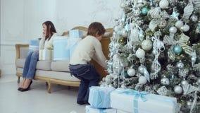 De gelukkige moeder die op de telefoon spreken terwijl haar weinig zoons brengende Kerstmis stelt op de bank voor stock footage