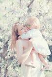 De gelukkige moeder die van het levensogenblikken kind in de zonnige lente koesteren Stock Foto
