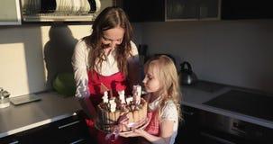 De gelukkige moeder en de dochter bereidden een verjaardagscake voor stock footage