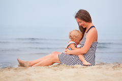 De gelukkige Moeder en de kleine dochter gaan langs de kust Stock Foto's