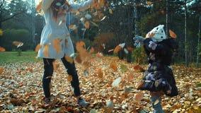 De gelukkige moeder en de dochter lopen langs bosweg Moeder en de dochter die in de herfstbos de lopen werpen op stock video