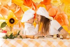 De gelukkige moeder en haar kind in de vorm van chef-koks bereiden een festiv voor Royalty-vrije Stock Afbeeldingen