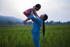 De gelukkige Moeder en haar kind spelen in openlucht het hebben van pret, Groene padieveld achtergrond stock fotografie