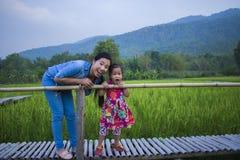 De gelukkige Moeder en haar kind spelen in openlucht het hebben van pret in Groene padieveld achtergrond royalty-vrije stock foto's