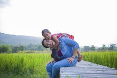 De gelukkige Moeder en haar kind spelen in openlucht het hebben van pret, Groene padieveld achtergrond stock afbeelding