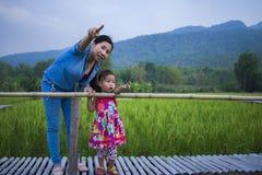 De gelukkige Moeder en haar kind spelen in openlucht het hebben van pret, en het richten bij iets in het Groene padieveld stock fotografie