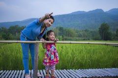 De gelukkige Moeder en haar kind spelen in openlucht het hebben van pret, en het richten bij iets in het Groene padieveld royalty-vrije stock afbeeldingen