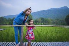 De gelukkige Moeder en haar kind spelen in openlucht het hebben van pret, en het richten bij iets in het Groene padieveld stock foto's