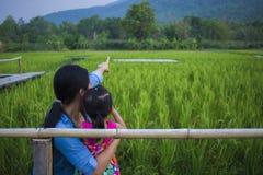 De gelukkige Moeder en haar kind spelen in openlucht het hebben van pret, en het richten bij iets in het Groene padieveld stock afbeelding