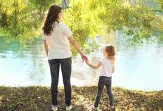 De gelukkige moeder en kindhanden van de dochterholding samen in de zomer Stock Afbeeldingen