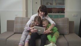 De gelukkige moeder en twee kinderen die op de bank zitten en bekijken de tablet Geïsoleerd op witte achtergrond stock videobeelden