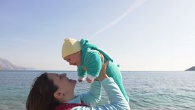 De gelukkige moeder houdt haar weinig kind op handen op het strand op een zonnige de lentedag stock footage