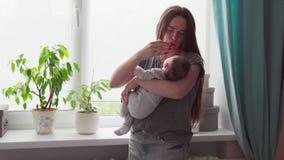 De gelukkige moeder kust en strijkt zacht haar baby stock video