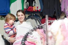 De gelukkige moeder met babymeisje kiest slijtage Royalty-vrije Stock Foto's