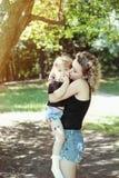 De gelukkige moeder met gelijkaardige dochter kijkt tedere kus stock afbeelding