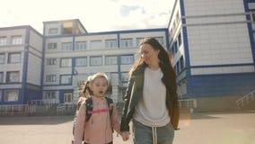 De gelukkige moeder met haar dochter in eenvormige school gaat naar huis stock videobeelden
