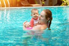 De gelukkige moeder met weinig babydochter zwemt in de pool bij de zomervakantie Zonnige dag keerkringen Zuigeling het letten op  royalty-vrije stock afbeeldingen