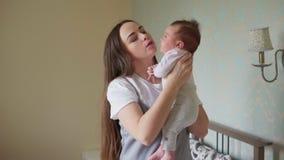 De gelukkige moeder neemt haar pasgeboren baby in wapens stock videobeelden