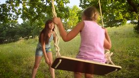 De gelukkige moeder schudt haar meisje op schommeling in park, schommeling op boomtak stock footage