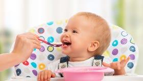 De gelukkige moeder voedt grappige baby van lepel Stock Afbeeldingen