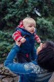 De gelukkige moeder werpt omhoog baby stock foto's