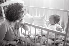 De gelukkige moeder zit daarna haar baby in de voederbak royalty-vrije stock fotografie