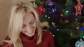 De gelukkige moeder zit onder de nieuwe jaarboom met fotoalbum in haar handen stock footage