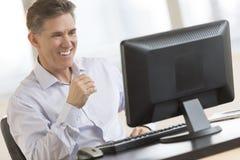 De gelukkige Monitor van Zakenmanlooking at computer royalty-vrije stock fotografie