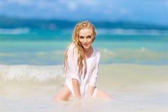 De gelukkige mooie blondevrouw met lang haar kleedde zich in wit stock afbeeldingen