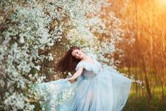 De gelukkige mooie jonge vrouw met lang zwart gezond haar geniet van verse bloemen en zonlicht in bloesempark bij zonsondergang Royalty-vrije Stock Foto's