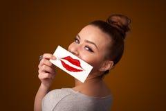De gelukkige mooie kaart van de vrouwenholding met het teken van de kuslippenstift stock foto