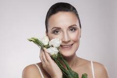 De gelukkige mooie rijpe vrouw met perfecte huid en de oude rimpels zijn mager op bloemen met toothy glimlach Het Concept van de  stock foto's