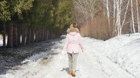 De gelukkige mooie vrouw loopt in het de winterbos op een zonnige dag Langzame Motie stock video
