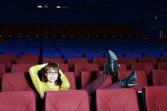 De gelukkige mooie vrouw in rode glazen hief haar benen op stoel op royalty-vrije stock afbeeldingen