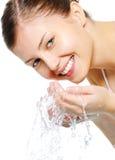 De gelukkige mooie vrouw wast haar gezicht Stock Foto's