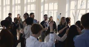 De gelukkige multi etnische bedrijfsmensen groeperen dansend samen het vieren vakantie op modern licht kantoor, werkplaatspartij stock videobeelden