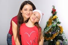 De gelukkige natuurlijke glimlachende moeder omhelst haar leuke dochter in de hoed van de Kerstman op achtergrond van de de booms stock foto's