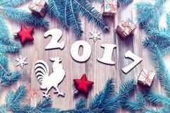 De gelukkige Nieuwjaar 2017 achtergrond met 2017 cijfers, Kerstmisspeelgoed, spar vertakt zich en het symbool van het haannieuwja Royalty-vrije Stock Foto's
