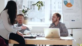 De gelukkige ontspannen jonge bedrijfsmensen werken bij lichte gezonde moderne werkplaats, het chef- zakenman spreken aan collega stock footage
