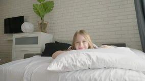 De gelukkige ontwaken van het meisjeskind op het bed in de ochtend Gezondheid, schoonheids en kinderjarenconcept stock footage