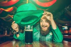 De gelukkige opgewekte jonge mens in groen kostuum zit bij lijst in bar Hij houdt hoed boven mok donker bier Jonge mensenglimlach royalty-vrije stock foto