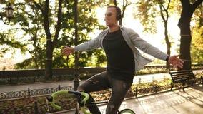 De gelukkige opgewekte jonge personenvervoerfiets in het park en luistert aan de muziek in zwarte hoofdtelefoons Mens met uitgest