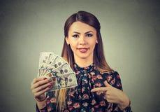 De gelukkige opgewekte succesvolle jonge het gelddollar van de bedrijfsvrouwenholding factureert ter beschikking Stock Foto