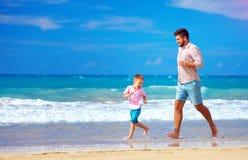 De gelukkige opgewekte vader en de zoon die op de zomerstrand lopen, genieten van het leven Stock Foto's