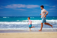 De gelukkige opgewekte vader en de zoon die op de zomerstrand lopen, genieten van het leven Royalty-vrije Stock Foto's