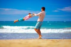 De gelukkige opgewekte vader en de zoon die pret op de zomerstrand hebben, genieten van het leven Royalty-vrije Stock Afbeelding