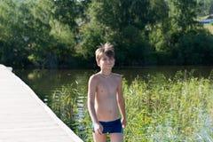 De gelukkige oude jongen 11 jaar gaat zwemmend op een houten pijler, op de achtergrond van de kust en het meer op een de zomer zo royalty-vrije stock foto's