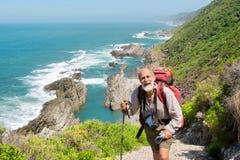 De gelukkige oude mens bereikt enkel de bovenkant van heuvel Royalty-vrije Stock Foto's