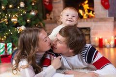 De gelukkige ouders en de kindjongen hebben een pret thuis dichtbij Kerstboom Vader, moeder, zoon het vieren Nieuwjaar samen Stock Foto