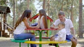 De gelukkige ouders met hun kleine kinderen rusten op speelplaats in park met hoge sparren in de zomerdag stock video